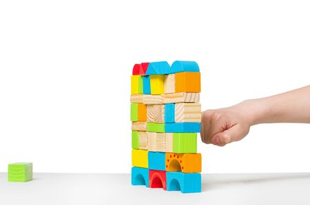 destroying: fist destroying house made of color wooden blocks