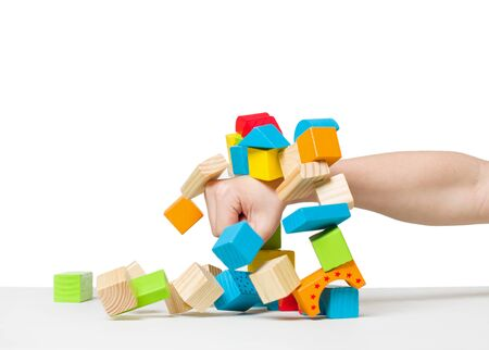 destroying: hand destroying house made of color wooden blocks