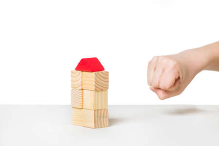 Human hand about to destroyi house made of wooden blocks photo