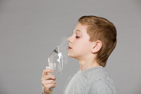 asthmatic: Boy breathing from inhalator mask releasing smoke on grey background
