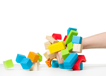 destroying: Human hand destroying house made of color wooden blocks копия