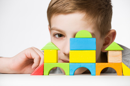 Portrait of a boy hiding behind house made of wooden blocks Stock Photo