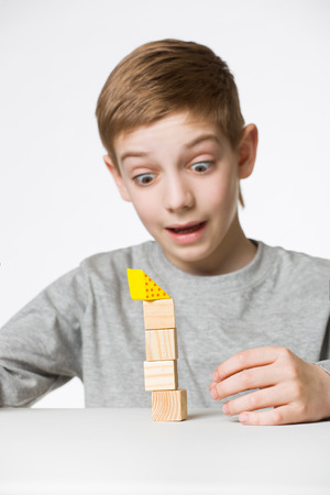 tower block: Portrait of a boy watching house made of wooden blocks fall
