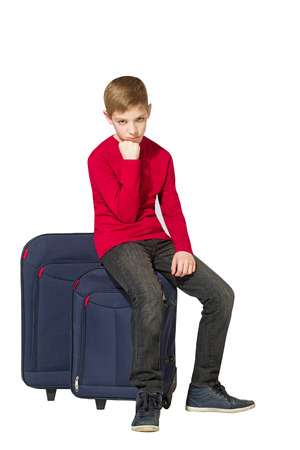 Sad boy sitting on travel bags isolated on white photo