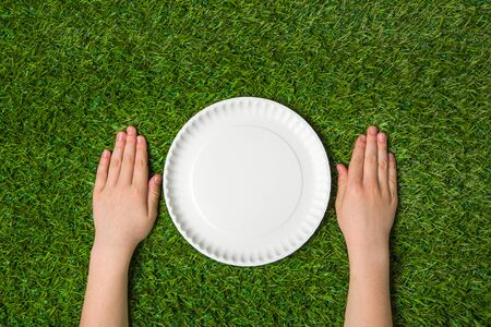 paper plates: Hands lying near empty paper plate on green grass