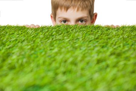 peeping: Boy peeping out through green grass Stock Photo