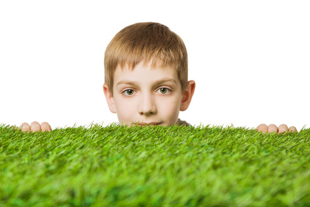 Portrait of a boy peeping out through green grass