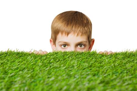 peeping: Portrait of a boy peeping out through grass