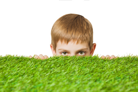 peeping: Boy peeping out through grass close up