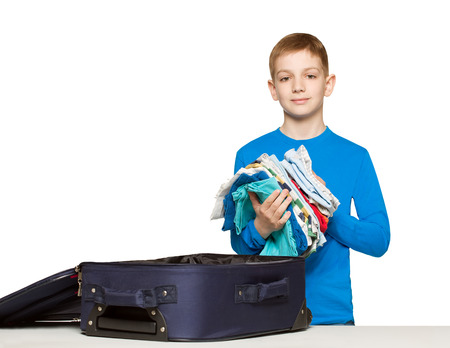 Boy going pack his luggage bag with clothes
