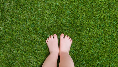 Baby legs standing  on green grass Stock Photo