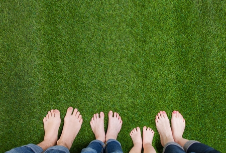 Family legs standing on green grass