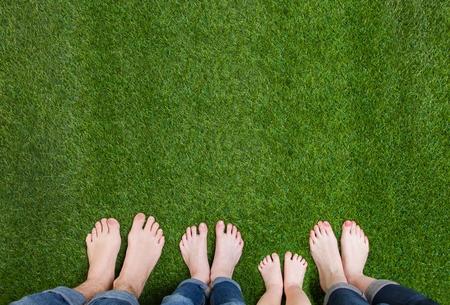 Family legs standing on green grass