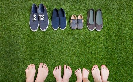 pie bebe: Piernas de la familia y los zapatos de pie sobre la hierba verde Foto de archivo