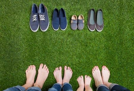 家族のジーンズの足や靴の草の上に立って