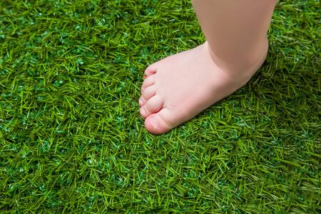 foot care: Baby bare leg standing  on green grass