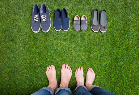 boy feet: Men and woman legs with shoes standing  on grass