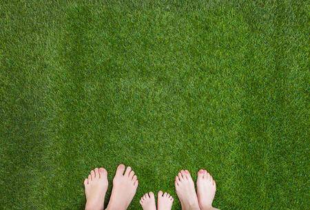 緑の草の上に一緒に立って家族の足