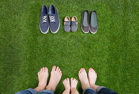 Family legs in jeans and shoes standing  on grass Stock Photo