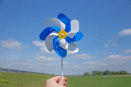 hand over: Hand holding pinwheel over horizon