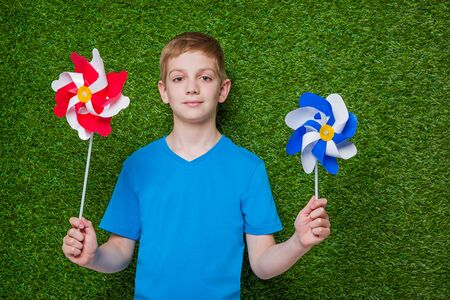 pinwheels: Boy holding red white and blue pinwheels over green grass Stock Photo