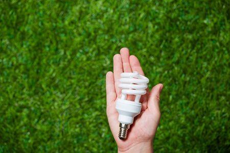 human energy: Human hand holding energy saving lamp over green grass