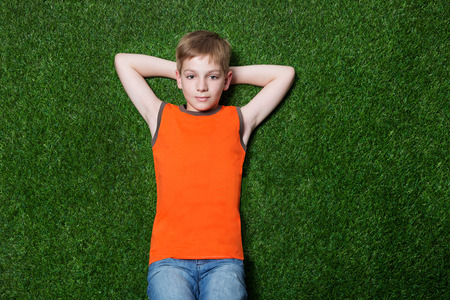 Boy lying and dreaming on green summer grass