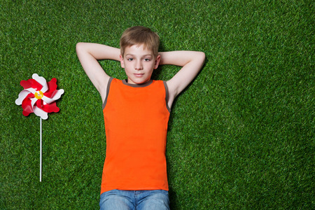 Boy lying with pinwheel and dreaming on green summer grass