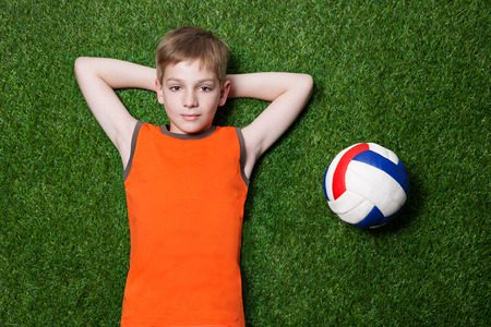 Boy lying with ball and dreaming on green summer grass