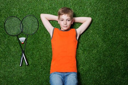 Boy lying with badminton racket and dreaming on green summer grass