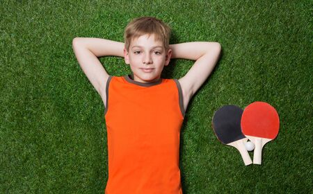 Boy lying with tennisracket and dreaming on green summer grass