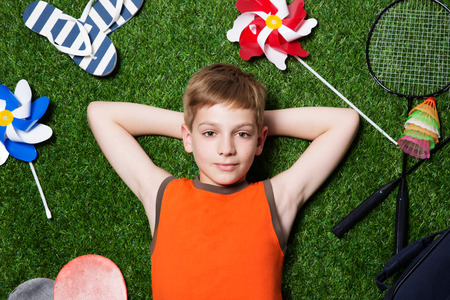 Boy lying with sport equipment and dreaming on green summer grass