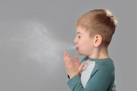 Unhealthy boy snezzing very hard over grey background