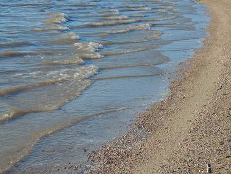 shore line: Coast line with waves on water and gravel on the shore