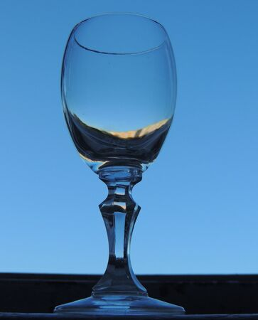 sill: Empty glass on window sill with clear sky in the background Stock Photo