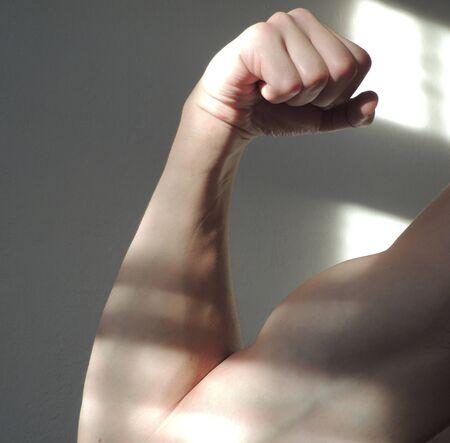 flexed: Light tone skinned arm with biceps flexed
