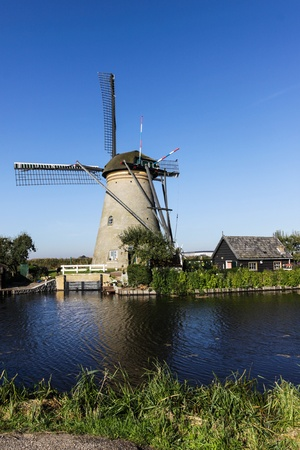 Windmill with house on the river photo