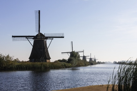 Line of windmills on the river photo