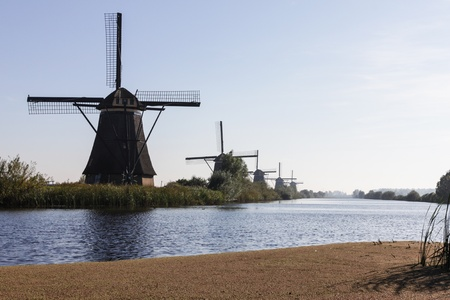 Line of windmills on the river in Holland photo