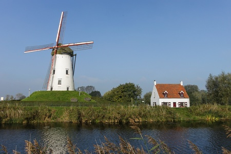 White windmill with house on the river photo