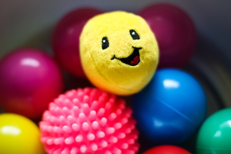 snugly: Yellow smile plush toy in the pile of round color balls Stock Photo