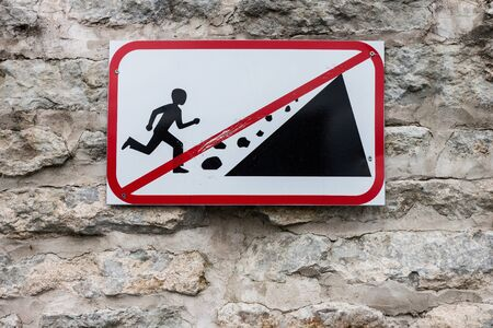 Falling rock sign on the wall Stock Photo - 13554230