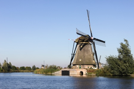 White windmill and house near river in Holland photo
