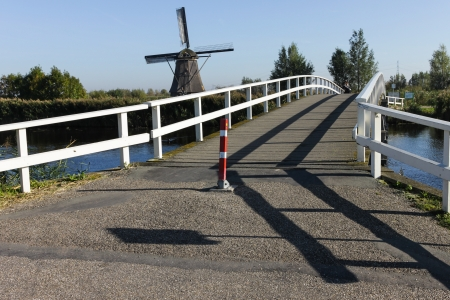 Bridge and windmill on the river in Holland photo