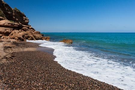 Beautiful small pebble beach on the coast of Costa Dorado, Spain. With rock photo