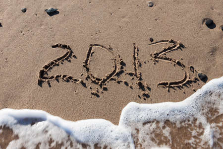 Numbers 2013 on sea beach sand with tide wave water Stock Photo - 14258429