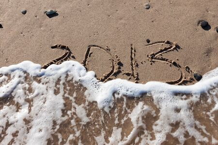 Numbers 2013 on the beach sand with wave water Stock Photo - 14258427
