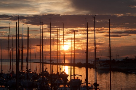 Sailboats in harbor with sunset and clouds photo