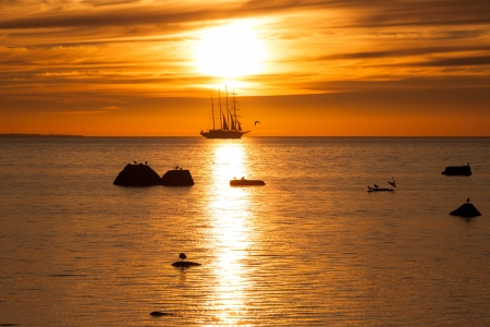 Old tall sail ship silhouette in sunset in sea photo
