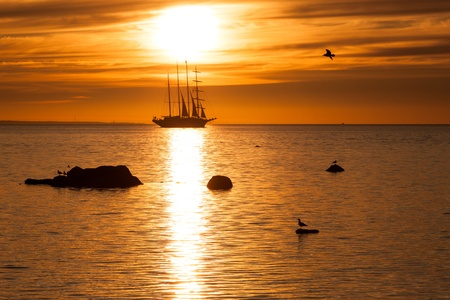 Old tall sail ship silhouette in sunset in Baltic sea photo